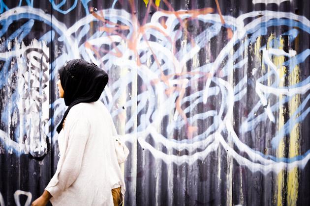woman walking past graffitti - brick lane, london